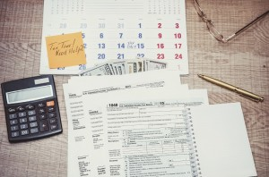 Tax form with calendar, pen, calculator, notepad and glasses. to