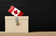 White ballot box and Canadian flag textured vote in front of blackboard. Horizontal composition. Election concept.
