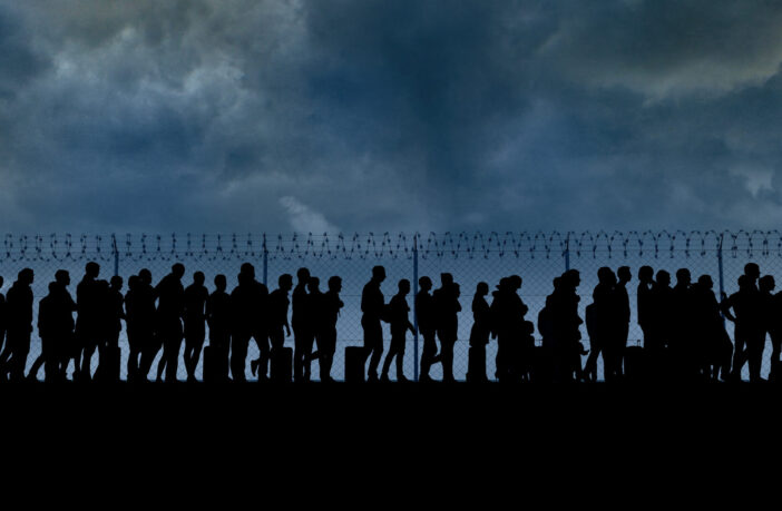 refugees and immigrants standing in front of a border fence